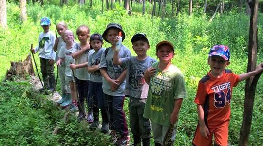Row of kids on a log.